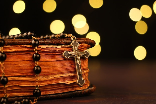 Bible and rosary close-up with bokeh lights