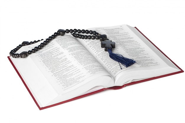 Bible on a white background. sacred book and wooden rosary.