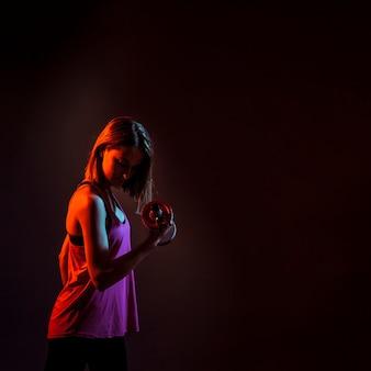 暗い、集中した女性のトレーニングbicep