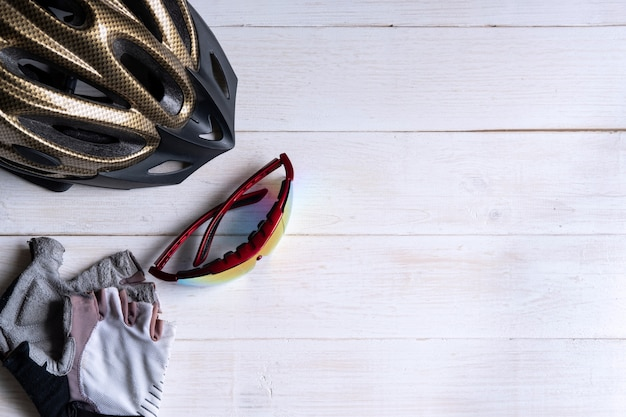 Bicycle accessories on white wooden table with copy space