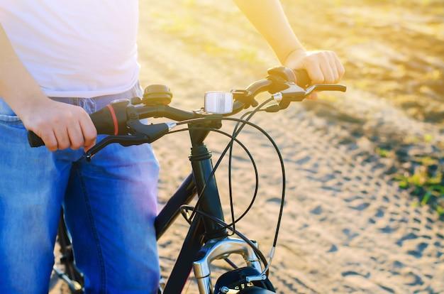 自転車と自然の男をクローズアップ、旅行、健康的なライフスタイル、田舎の散歩。自転車のフレーム。