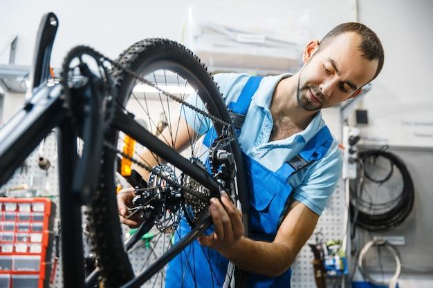 Сборка велосипеда в мастерской, установка цепи