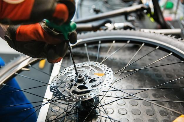 Сборка велосипедов в мастерской, человек устанавливает тормозной диск