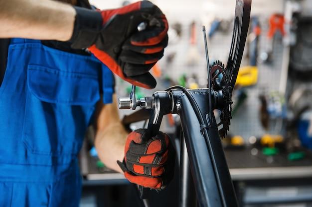 Сборка велосипедов в мастерской, человек устанавливает кривошип