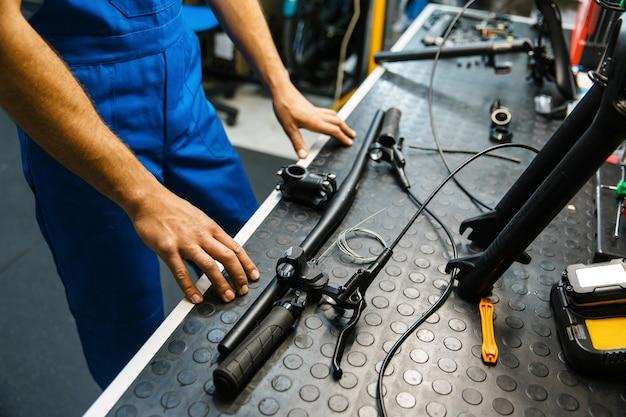 Сборка велосипедов в мастерской, человек устанавливает руль