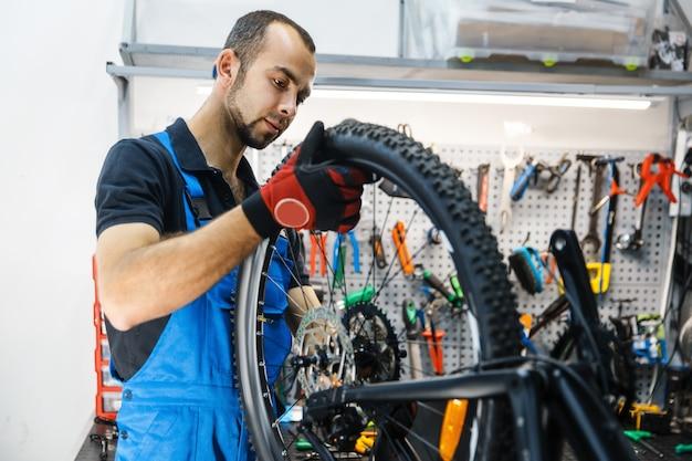 Сборка велосипедов в мастерской, человек устанавливает заднее колесо