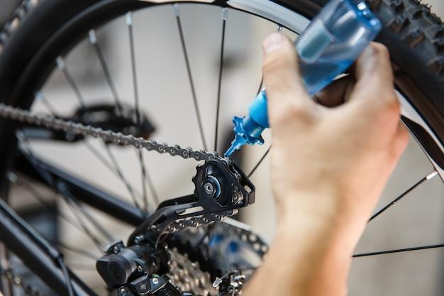 Сборка велосипедов в мастерской, человек смазывает цепь