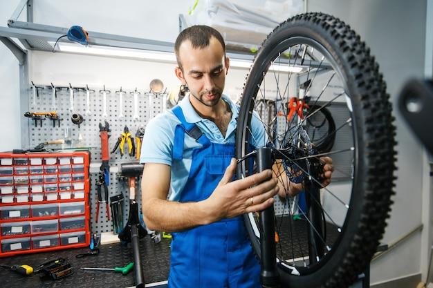 Сборка велосипедов в мастерской, мужчина устанавливает цепь
