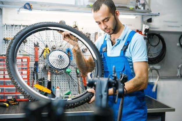 Сборка велосипеда в мастерской, установка колес