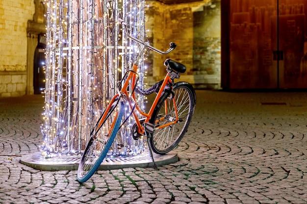 輝くランタンの夜の花輪で伝統的なヨーロッパのクリスマスマーケットで自転車が木を飾る