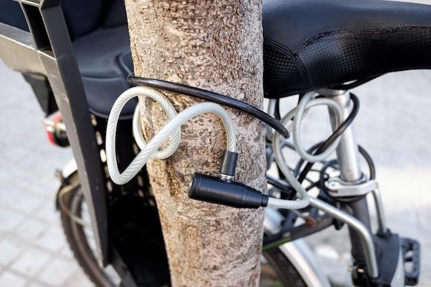 Велосипед, прикованный цепью к стволу дерева на дороге общего пользования, с замком.