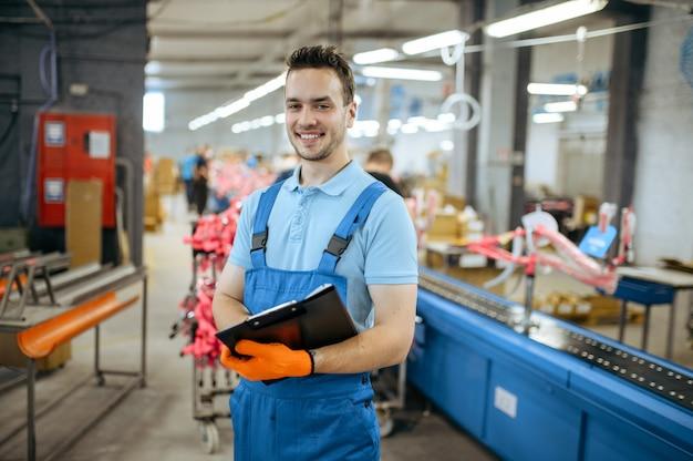 自転車工場、自転車組立ラインでノートを持って笑顔の労働者。制服を着た男性整備士がワークショップにサイクルパーツを取り付ける