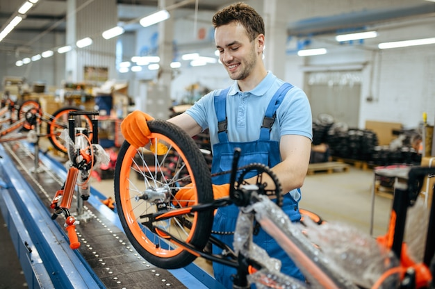 Bicycle factory, worker at assembly line, wheel installation. male mechanic in uniform installs cycle parts in workshop
