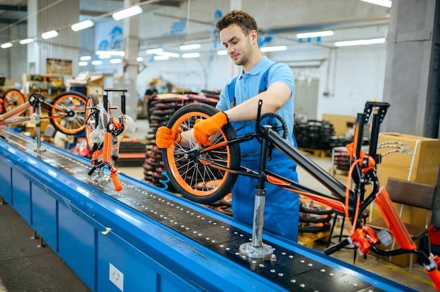 自転車工場、組立ラインの作業員、ホイールの取り付け。制服を着た男性整備士がワークショップにサイクルパーツを取り付ける
