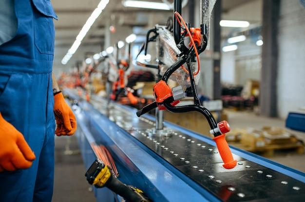 自転車工場、労働者は自転車の組立ラインをチェックします。制服を着た男性整備士がワークショップにサイクルパーツを取り付ける