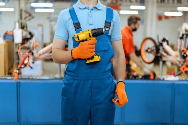 自転車工場、労働者は自転車の組立ラインで電動ドライバーを持っています。制服を着た男性整備士がワークショップにサイクルパーツを取り付ける