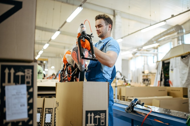 自転車工場、労働者は十代の自転車を箱に詰めます。制服を着た男性メカニックがサイクルパーツ、ワークショップの組立ラインを設置