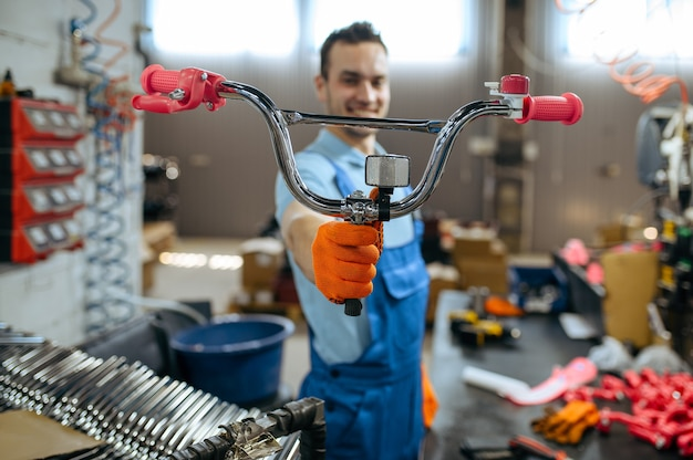 Bicycle factory, worker shows girl's bike handlebar. male mechanic in uniform installs cycle parts, assembly line in workshop
