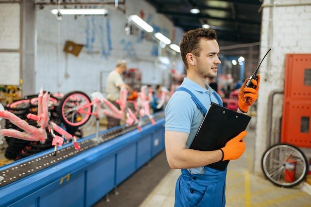 自転車工場、トランシーバーを持った労働者が自転車の組立ラインでポーズをとる。制服を着た男性整備士がワークショップにサイクルパーツを取り付ける