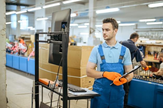 自転車工場、自転車組立ラインでノートのポーズをとる労働者。制服を着た男性整備士がワークショップにサイクルパーツを取り付ける