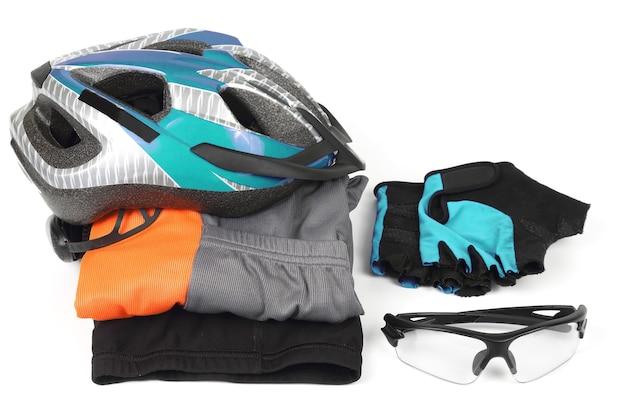 白い背景の上の自転車のヘルメット、メガネ、衣類。スポーツ用品