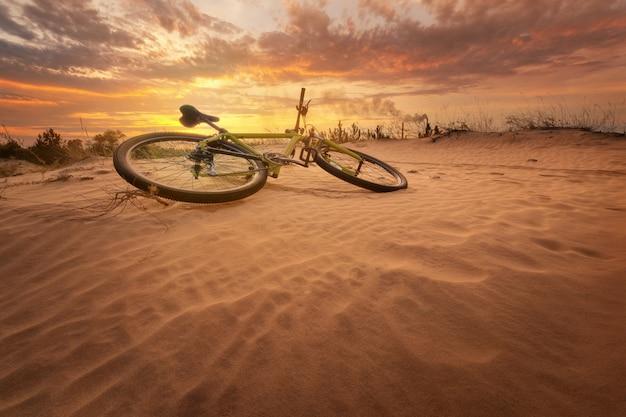Велосипед в пустыне на желтом жарком закате