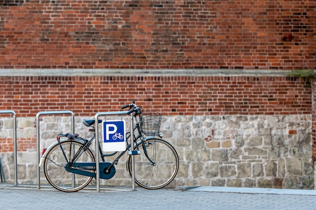 The bicycle is parked on the parking lot at the edge of the old town street.