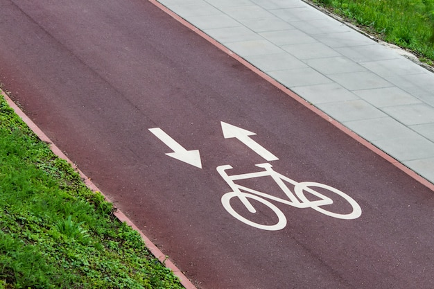 Bicycle lane signs with arrows on the red city bike pathway