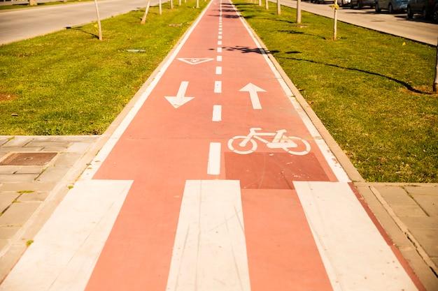 緑の芝生の間の印が付いている自転車レーン