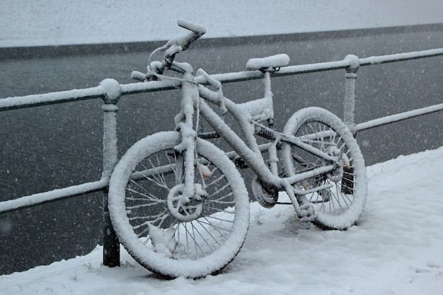 Bicycle leaned against a fence covered in snow