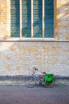 Bicycle leaning on old stone wall