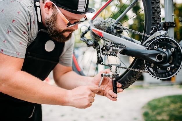 Веломеханик в фартуке регулирует велосипедную цепь