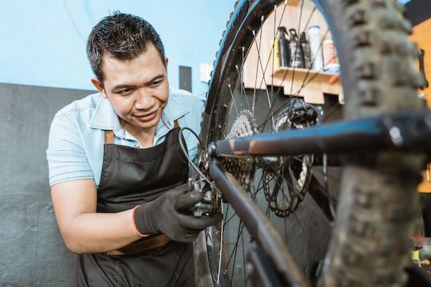 앞치마에 있는 자전거 정비사는 문제를 해결하는 동안 후방 기계를 확인합니다.