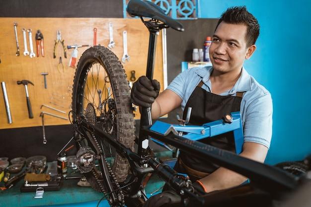 앞치마를 입은 자전거 정비사는 자전거 안장 마운트를 부착할 때 장갑을 착용합니다.