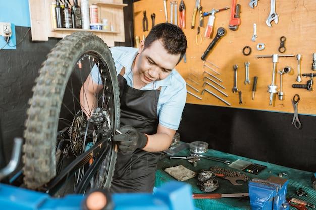 앞치마를 입은 자전거 정비사, 카피스페이스가 있는 바퀴와 차축 설치