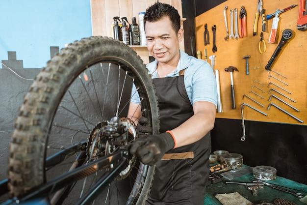 문제를 해결하는 동안 바퀴를 설치하는 앞치마의 자전거 정비사