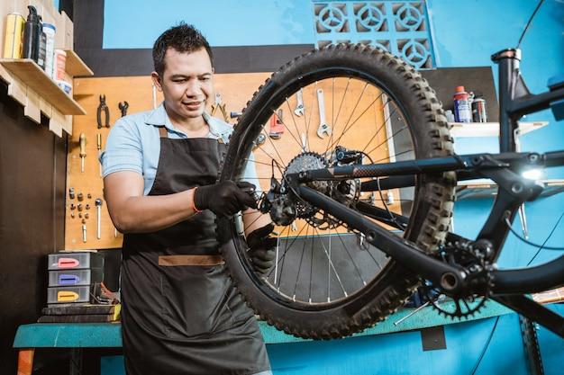 앞치마를 입은 자전거 정비사는 문제를 해결하는 동안 스포크를 조입니다.
