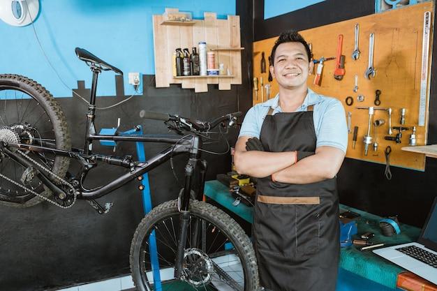 자전거 옆에 서 있는 동안 교차 손으로 자전거를 들고 웃는 앞치마에 자전거 정비사