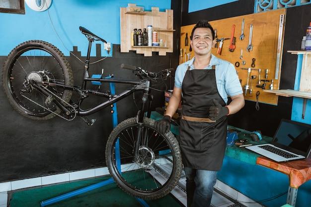 자전거 옆에 서 있는 동안 엄지손가락으로 자전거를 들고 웃는 앞치마에 자전거 정비사
