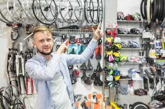 Bicycle mechanic pointing upwards in workshop