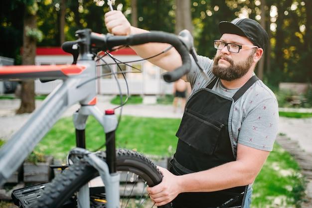 Веломеханик ремонтирует велосипед, вид сверху