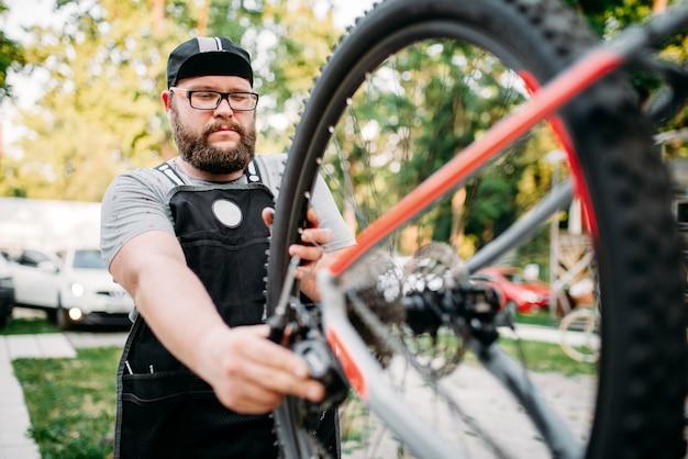 Веломеханик ремонтирует велосипед со сломанным переключателем