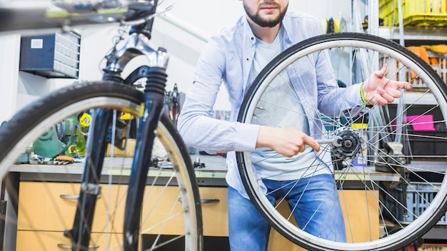 Bicycle mechanic repairing bicycle tire with wrench