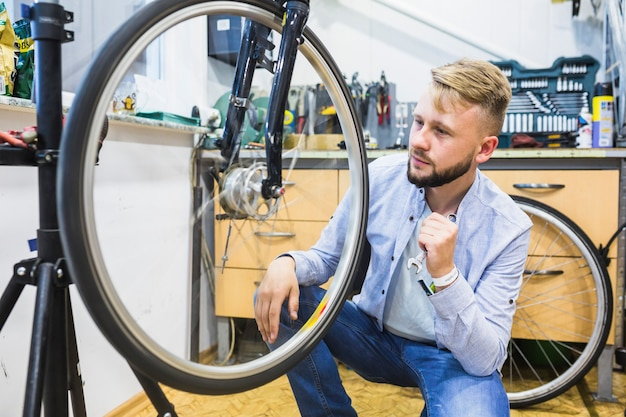 Bicycle mechanic with wrench looking at bicycle tire