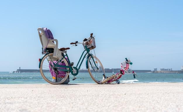 Велосипед матери и дочери, остановился на пляже в приятный день семейной прогулки