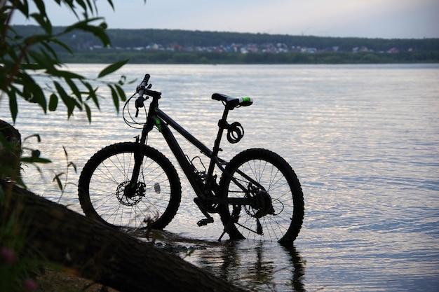 夕日の光の中でビーチで自転車、海の近くの砂丘に自転車を駐車