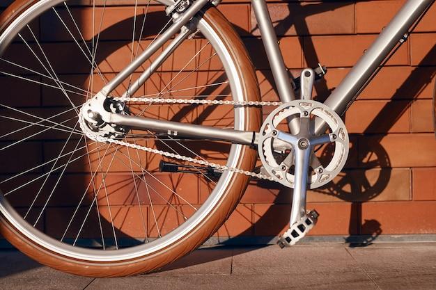 Велосипед припаркован у кирпичной стены