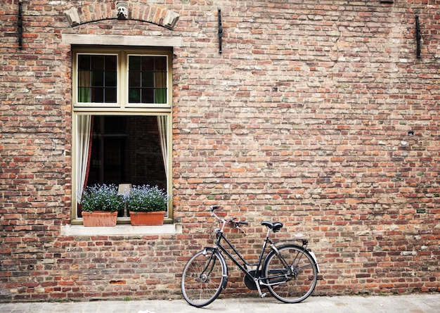 브뤼헤의 폐쇄 된 창문 밖에 주차 된 자전거