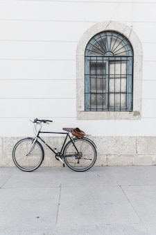 Bicycle parked on white wall with window