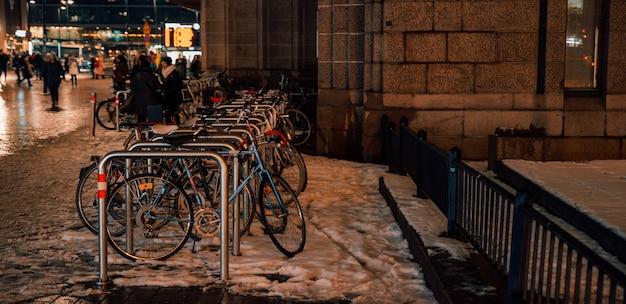 Велосипедная парковка на открытом воздухе зимним вечером в городе